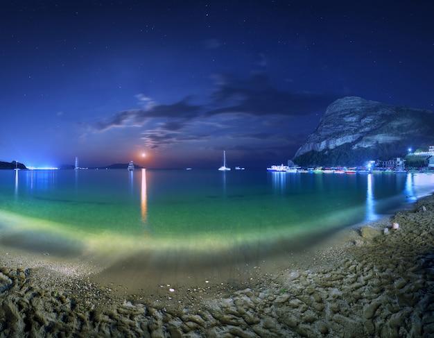 Красивый ночной пейзаж на берегу моря с желтым песком