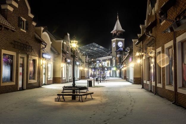 Красивый ночной пейзаж зимней улицы с башенными часами