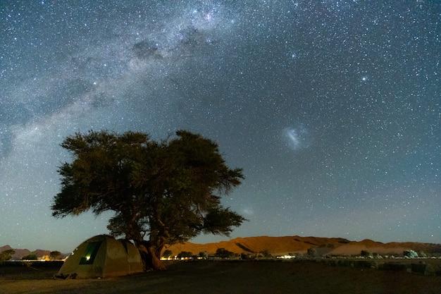 Красивый ночной пейзаж с видом на млечный путь и галактическое ядро над кемпингом в национальном парке этоша, намибия