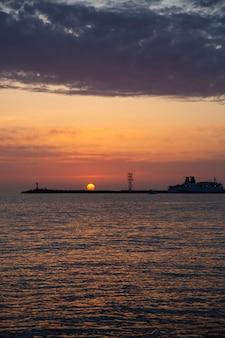 輝く灯台の後ろの美しい夜空。海に沈む夕日と小さな灯台
