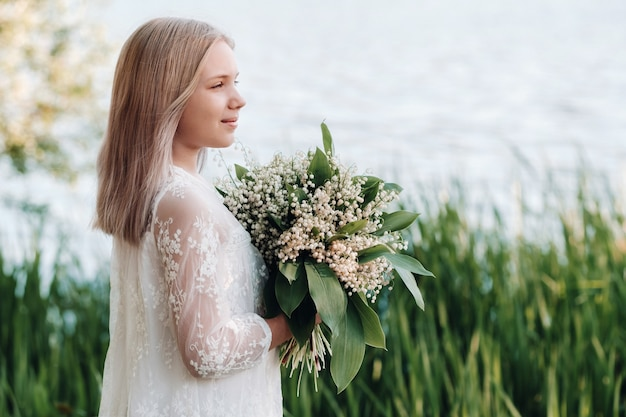 A beautiful nine-year-old blonde girl with long hair in a long white dress, holding a bouquet of lilies of the valley flowers