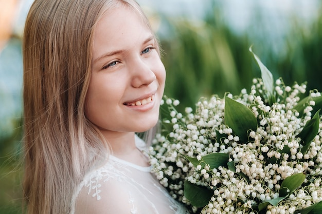 A beautiful nine-year-old blonde girl with long hair in a long white dress, holding a bouquet of lilies