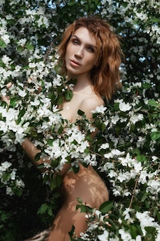 Beautiful nude art woman in branches and foliage of a flowering apple tree in nature. beautiful slim body, natural cosmetics and beauty. apple flowers on girl body