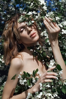 Beautiful nude art woman in branches and foliage
