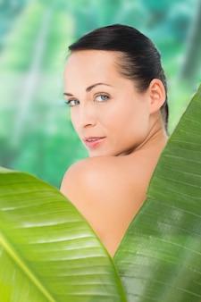 Красивая обнаженная брюнетка позирует с зелеными листьями