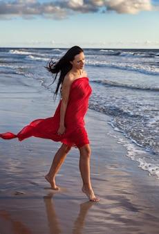 海沿いの自然を楽しむ赤い布で覆われた美しい裸の女の子。海岸の若い女性