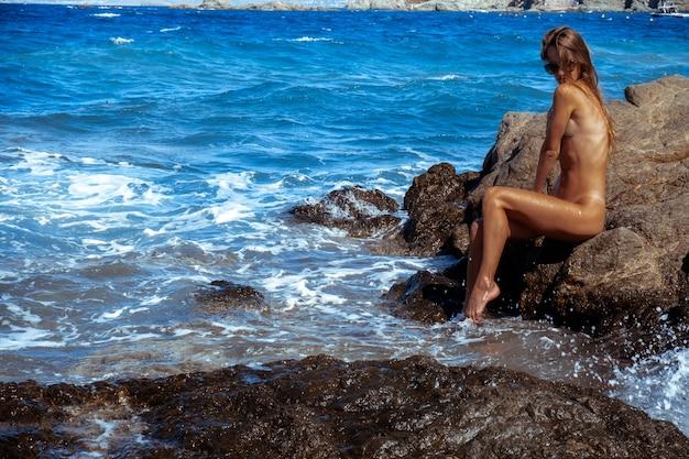 岩の多い海岸の美しい裸の女の子