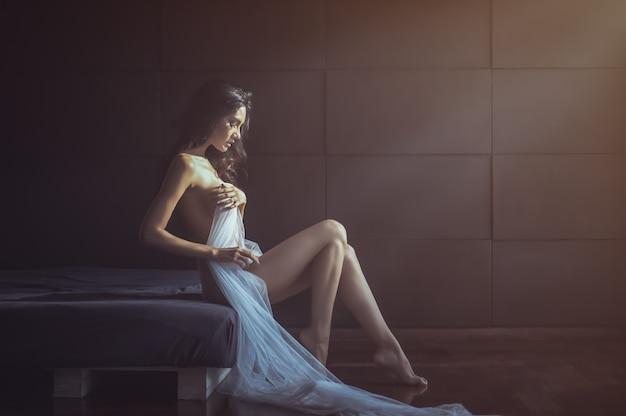エレガントなポーズで美しいヌードセクシーな女性。ファッションモデルの女の子の屋内の肖像画。