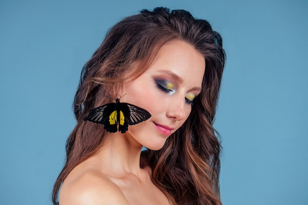 Красивая обнаженная женщина на синем фоне. идеальная кожа, профессиональный макияж и прическа девушки и красивая бабочка