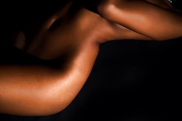 黒の背景の前に横たわっている美しいヌードの若い女性の体