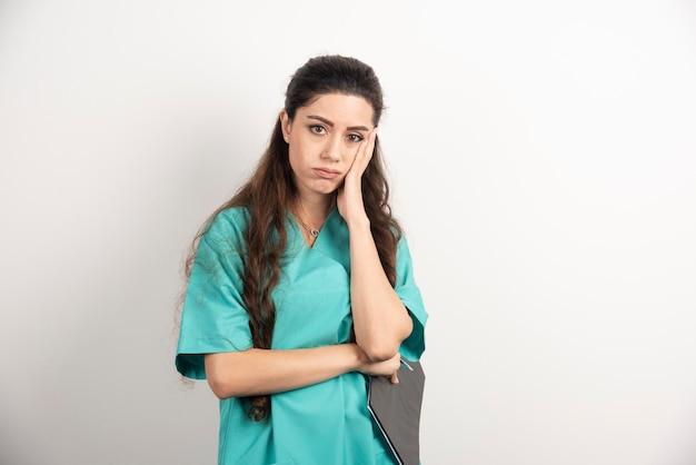 Bello ritratto dell'infermiera sulla parete bianca.