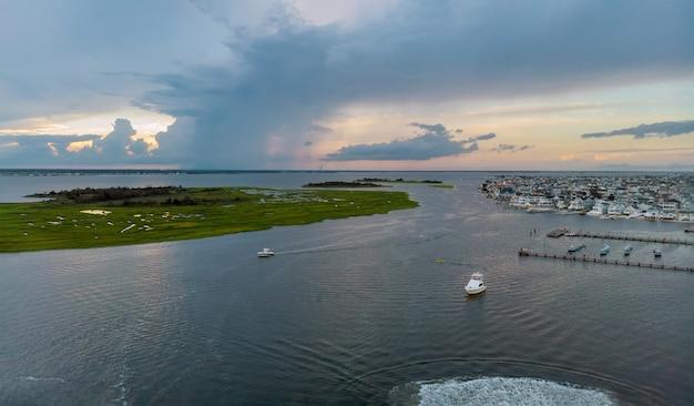Красивая океанская пристань для яхт с высоты птичьего полета в прибрежном жилом районе на пляже, лодки, пирсы