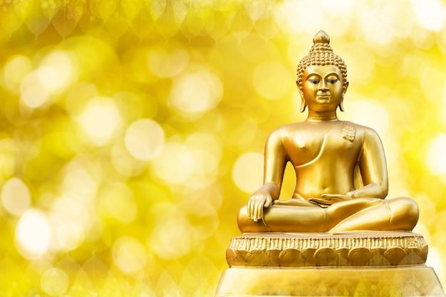 Красивый золотой статуи будды на золотом желтом bokeh.
