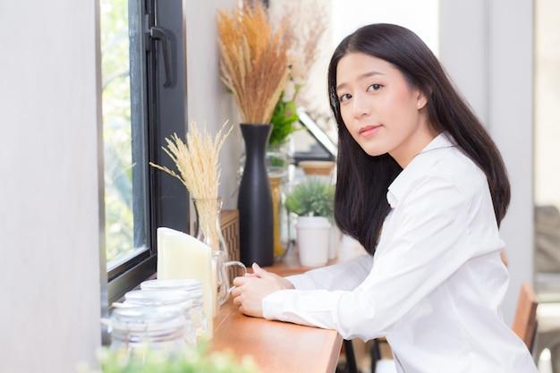 肖像画の美しいアジアの若い女性は、オンラインでコーヒーショップに座って働いています。