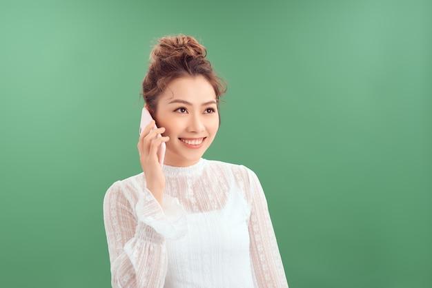 Красивый телефон разговора женщины портрета молодой азиатский умный над зеленым фоном.