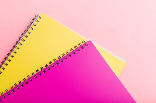 Beautiful office stationery flat lay with two notebooks pink and yellow color, on the bright desk