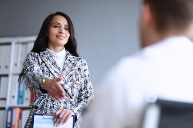 美しいオフィスの女性は男に彼女の手を差し出します