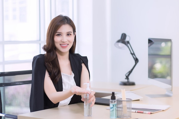A beautiful office woman is sitting and pressing an alcohol gel to happily wash hands at work