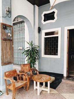 Красивое старое синее здание с аркой, окном, дверью и деревянным столом с двумя стульями