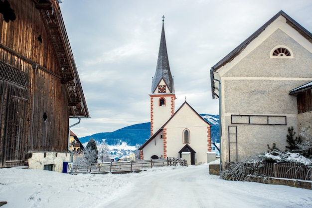 Beautiful old catholic church in small austrian town covered by snow