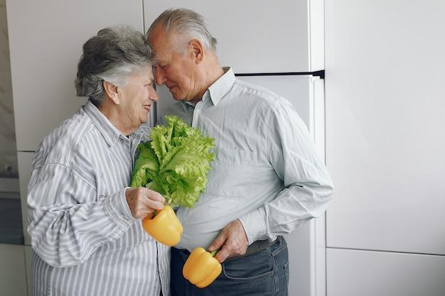 아름 다운 오래 된 부부는 부엌에서 음식을 준비