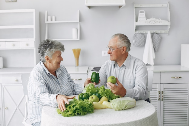 Beautiful old couple prepare food in a kitchen