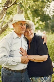 美しい老夫婦は夏の庭で時間を過ごす