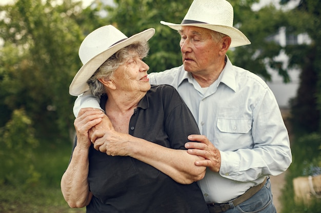 Beautiful old couple spend time in a summer garden