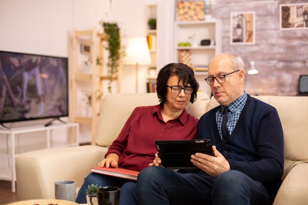 Красивая пожилая пара с помощью цифрового планшета, чтобы пообщаться со своей семьей. пожилые люди, использующие современные технологии