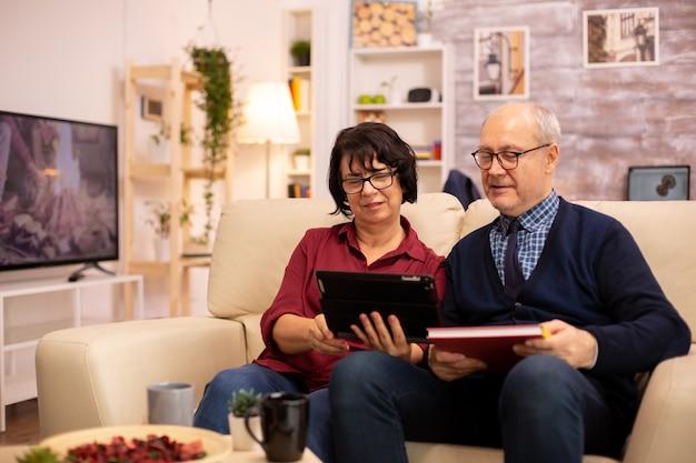 디지털 태블릿을 사용하여 가족과 채팅하는 아름다운 노부부. 현대 기술을 사용하는 노인