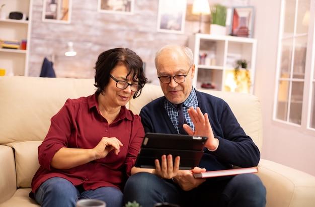 デジタルタブレットを使用して家族とチャットする美しい老夫婦。現代の技術を使用している高齢者