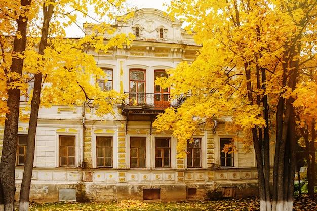 Красивый старый дом среди осенних желтых деревьев