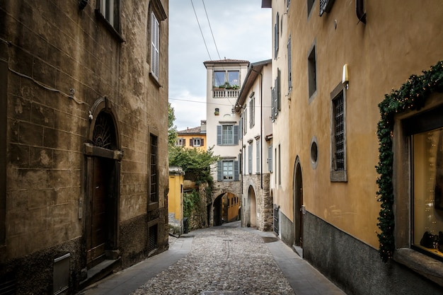 Beautiful old narrow street of small medieval city citta alta, perspective of street in bergamo, italy.