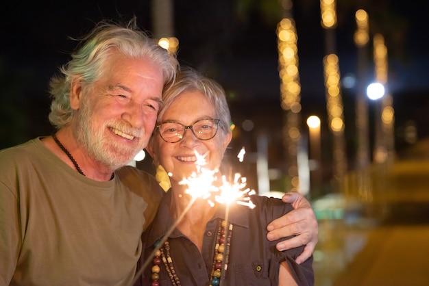 밤에 야외에서 아름다운 노부부가 반짝 조명으로 즐거운 시간을 보내고 있습니다. 사랑으로 포옹 하는 두 웃는 은퇴한 사람들
