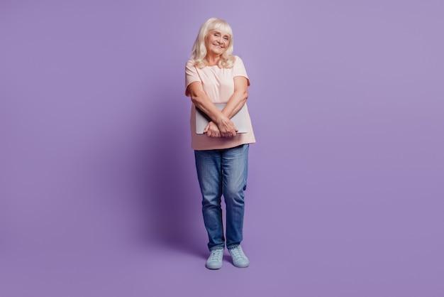 Красивая старая женщина нести ноутбук на фиолетовом фоне