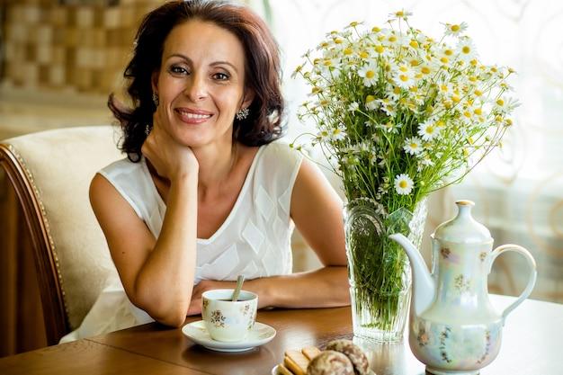 Красивая старушка в белой блузке сидит за круглым столом с букетом ромашек