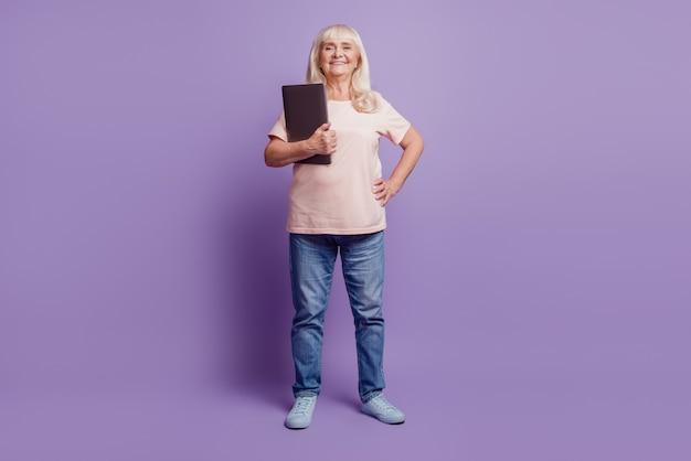 Красивая старуха менеджер держит ноутбук на фиолетовом фоне
