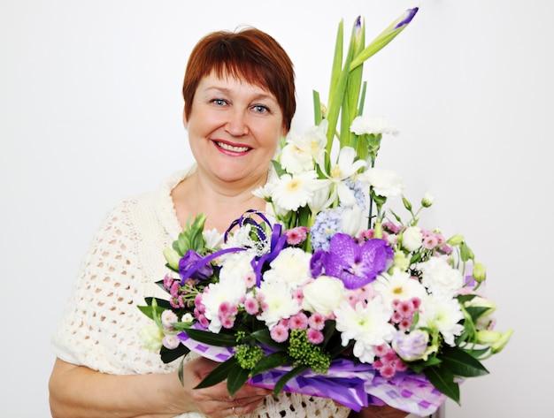 花の生け花を持っている美しい年上の女性