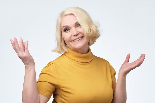 黄色いセーターを笑顔で美しい年上の女性