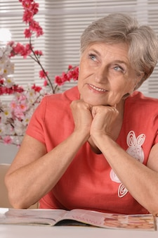 Beautiful older woman reading magazine with flowers on background