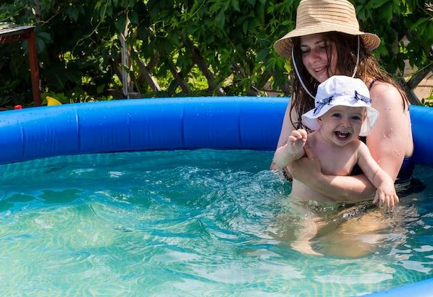 아름다운 한 살짜리 소녀는 더운 날 엄마와 함께 풍선 수영장에서 목욕하고 놀고 있습니다.