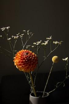 美しいオレンジ色の日当たりの良いダリアの花黄色のクラスペディアと白いドライフラワーモダンなブーケ...