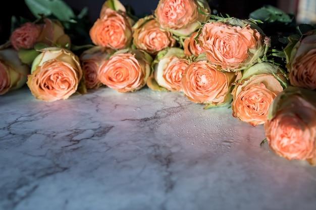 아름 다운 오렌지 산호 모란 모양의 대리석 배경에 장미와 장미 꽃다발 부드러운 꽃이 만발한 핑크 장미 꽃.