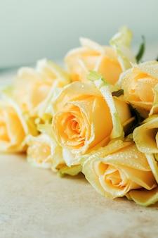 明るいコンクリートの背景の上に美しいオレンジ色のバラ。水平方向の構成。バレンタインデーや結婚式おめでとうのテキスト。