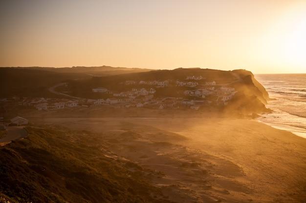 ポルトガルの海の海岸に沈む美しいオレンジ色の夕日。横ショット
