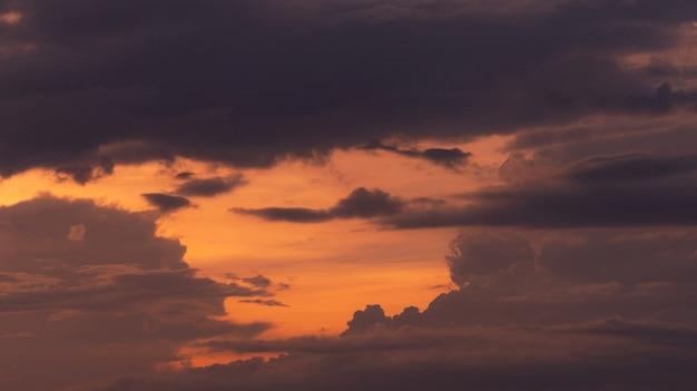 Красивое оранжевое закатное небо со слоями серых и темных облаков. живописный вид. красота в природе. сумеречное небо. небесное небо в сумерках для спокойного и мирного фона. романтическое закатное небо.