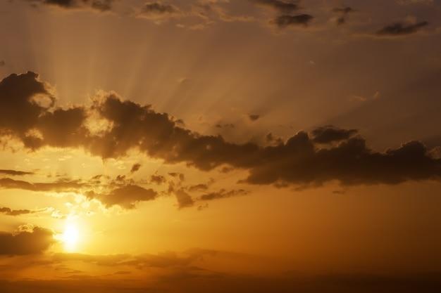 Красивое оранжевое небо заката с солнечными лучами.