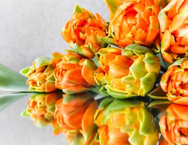 背景のグリーティングカードに最適な鏡の上の美しいオレンジ色のチューリップ