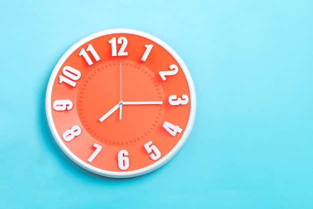 Beautiful orange wall clock on blue background