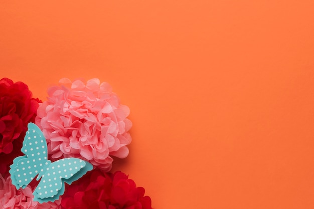 Beautiful origami paper flowers and polka dotted blue butterfly on orange backdrop